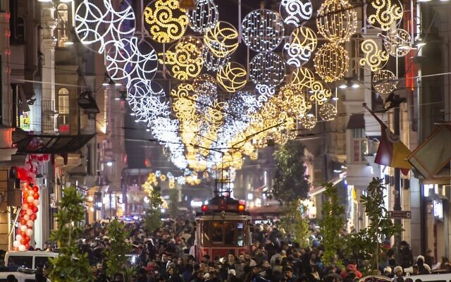 People walk past a historical tramway under Christmas light decorations on Istiklal street during preparations to celebrate the New Year 2020 in Istanbul on December 31, 2019. (Yasin Akgul/AFP)