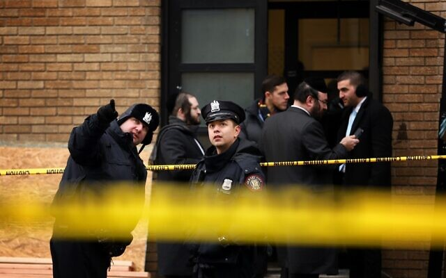 Police officers look at bullet holes in the windows of a school across the street from the JC Kosher Supermarket on December 11, 2019 in Jersey City, New Jersey. (Rick Loomis/Getty Images/AFP)