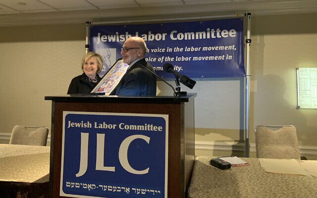 Jewish Labor Committee President Stuart Appelbaum, left, presenting Hillary Clinton with a poster portraying the Jewish immigrant experience in the US at the Sheraton New York Times Square Hotel, December 9, 2019. (Josefin Dolsten via JTA)