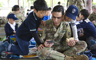 A US Army soldier shows elementary school students a game on his cellphone while eating lunch during an Earth Day event on April 24, 2019, in Japan. (U.S Army photo by Noriko Kudo)