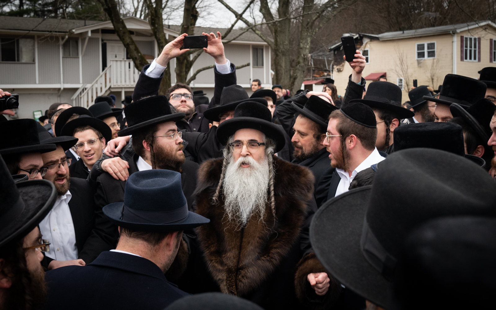 Rabbi Chaim Leibish Rottenberg, center, outside his home, a day after a knife-wielding attacker injured five inside during a Hannukah ceremony. (Luke Tress/Times of Israel)