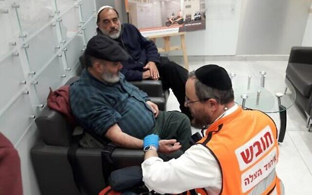 A paramedic examines David Ben Avraham (c) after his release from Palestinian prison, as behind him friend Haim Pereg looks on (United Hatzalah)