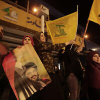 In this Oct. 25, 2019 file photo, supporters of Hezbollah leader Hassan Nasrallah hold his pictures and waves Hezbollah flags in the southern suburb of Beirut, Lebanon.  (AP Photo/Hassan Ammar)