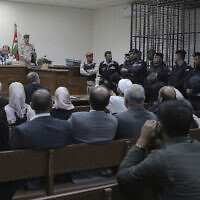 Israeli Konstantin Kotov stands in the defendant's cage during an appearance before a state security court where he was charged with illegally entering the country and possessing drugs, in Amman, Jordan, Monday Dec. 2, 2019. (AP Photo/Raad Adayleh)