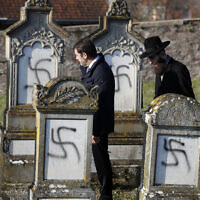 Illustrative: French Interior Minister Christophe Castaner, center, followed by Strasbourg Chief Rabbi Harold Abraham Weill, second right, walk amid vandalized tombs in the Jewish cemetery of Westhoffen, west of the city of Strasbourg, eastern France, December 4, 2019. (Jean-Francois Badias/AP)