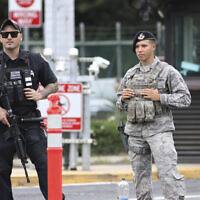 Security stands guard outside the main gate at Joint Base Pearl Harbor-Hickam, in Hawaii, Wednesday, Dec. 4, 2019. (AP Photo/Caleb Jones)