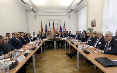 Officials at a bilateral meeting as part of the closed-door nuclear talks with Iran in Vienna, Austria, Friday, Dec. 6, 2019. (AP Photo/Ronald Zak)