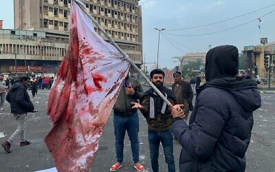 A protester holds a blood-stained flag at the site of a gunmen attack in Baghdad, Iraq, Saturday, Dec. 7, 2019 (AP/Ali Abdul Hassan)