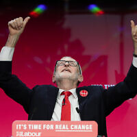 In this November 21, 2019 file photo Jeremy Corbyn, leader of Britain's opposition Labour Party gestures on stage at the launch of Labour's General Election manifesto, at Birmingham City University, England. (AP Photo/Kirsty Wigglesworth)