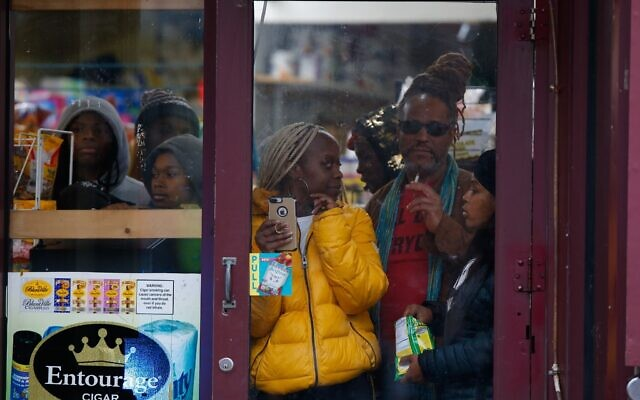 Bystanders look out from a store window as police officers arrive on the scene of a shooting in Jersey City, New Jersey, December 10, 2019. (AP Photo/Eduardo Munoz Alvarez)