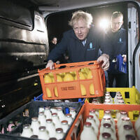 Britain's Prime Minister Boris Johnson loads a crate into a milk delivery van during a campaign visit in Leeds, England, December 11, 2019. (Stefan Rousseau/PA via AP)