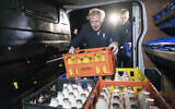 Britain's Prime Minister Boris Johnson loads a crate into a milk delivery van during a visit to Greenside Farm Business Park, as he campaigns for votes on the last day of campaigning ahead of a General Election, in Leeds, England, December 11, 2019.  (Stefan Rousseau/PA via AP)