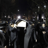Orthodox Jewish men carry the casket with Mindel Ferencz outside a Brooklyn synagogue, Wednesday, Dec. 11, 2019, in New York. Her funeral will be in Jersey City. Ferencz was killed Tuesday in the shooting inside a Jersey City, N.J., food market. (AP Photo/Mark Lennihan)