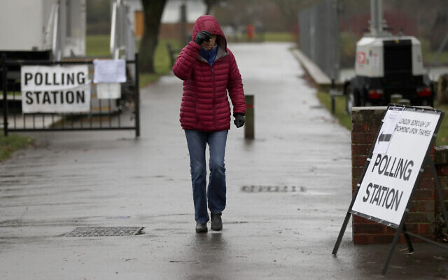 A woman leaves a polling station after voting in Twickenham, England, in the British general elections, December 12, 2019. (AP Photo/Frank Augstein)