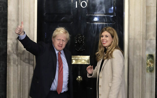 Britain's Prime Minister Boris Johnson and his partner Carrie Symonds wave from the steps of number 10 Downing Street in London, Friday, Dec. 13, 2019. Johnson's Conservative Party won a solid majority of seats in Britain's Parliament — a decisive outcome to a Brexit-dominated election. (AP Photo/Matt Dunham)
