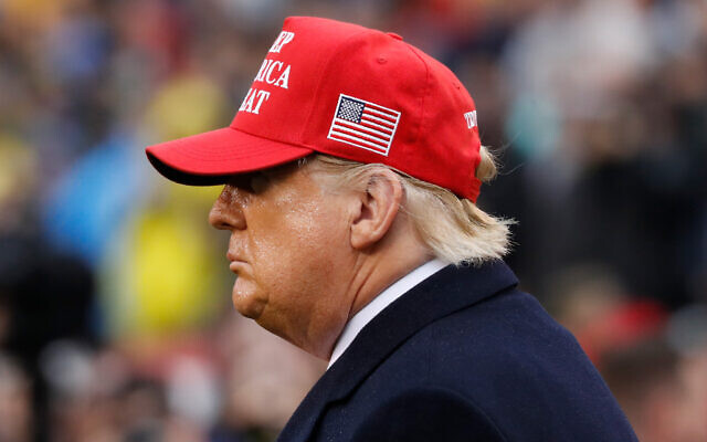 US President Donald Trump wears a red hat as he stands on the field before the Army-Navy college football game in Philadelphia, Saturday, Dec. 14, 2019. (AP Photo/Jacquelyn Martin)