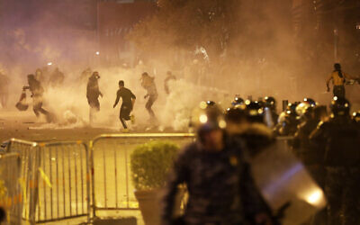 Anti-government protesters run away as the riot police fired tear gas against them during a protest in downtown Beirut, Lebanon, December 14, 2019. (AP Photo/Hussein Malla)