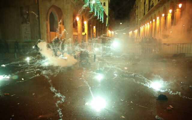 Anti-government protesters throw firecrackers against the riot police, background, during a protest near the parliament square, in downtown Beirut, Lebanon, Sunday, Dec. 15, 2019.  (AP Photo/Hussein Malla)