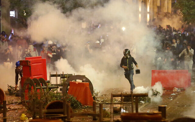 Anti-government protesters clash with the riot police, during a protest near the parliament square, in downtown Beirut, Lebanon, Sunday, Dec. 15, 2019.  (AP Photo/Hussein Malla)