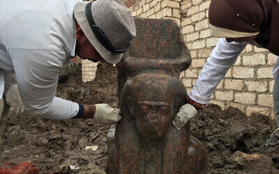 In this December 11, 2019, photo released by the Egyptian Ministry of Antiquities, archaeology workers clean a small pink granite statue of Ramses II, near the ancient pyramids of Giza, Egypt. (Egyptian Ministry of Antiquities via AP)
