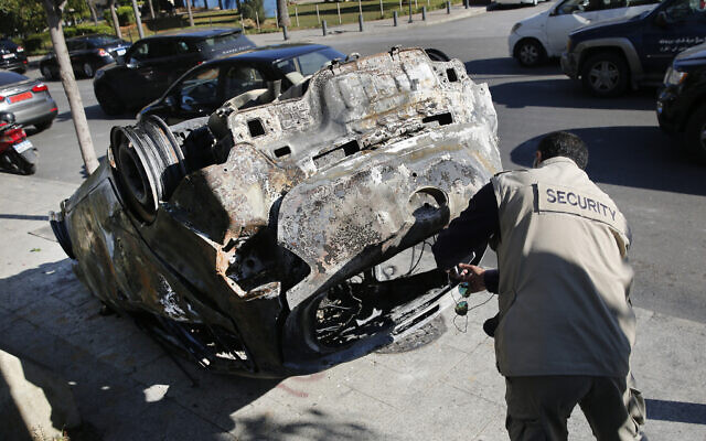A private security worker takes pictures of a burned car that was set on fire by supporters of the Shiite Hezbollah and Amal Movement groups, in Beirut, Lebanon, December 17, 2019. (Hussein Malla/AP)
