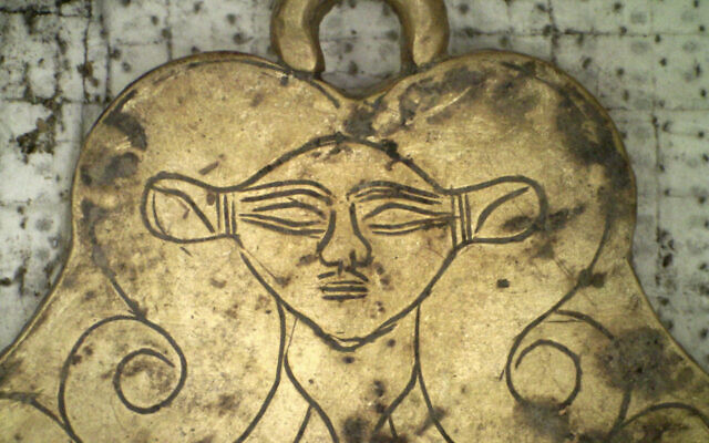 In this undated photo provided by the Greek Culture Ministry on, December 17, 2019, a golden pendant of the Egyptian goddess Hathor is seen that was found in a 3,500-year-old tomb discovered near the southwestern Greek town of Pylos. (Greek Culture Ministry via AP)