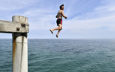 In this December 17, 2019 photo, a swimmer jumps from the Port Noarlunga Jetty in an effort to cool off in Adelaide, Australia. (David Mariuz/AAP Image via AP)
