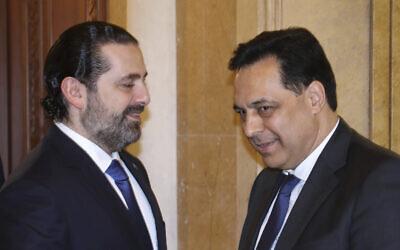 Lebanese Prime Minister-designate Hassan Diab, right, shakes hands with outgoing Prime Minister Saad Hariri, left, in Beirut, Lebanon, December 20, 2019 (Dalati Nohra via AP)