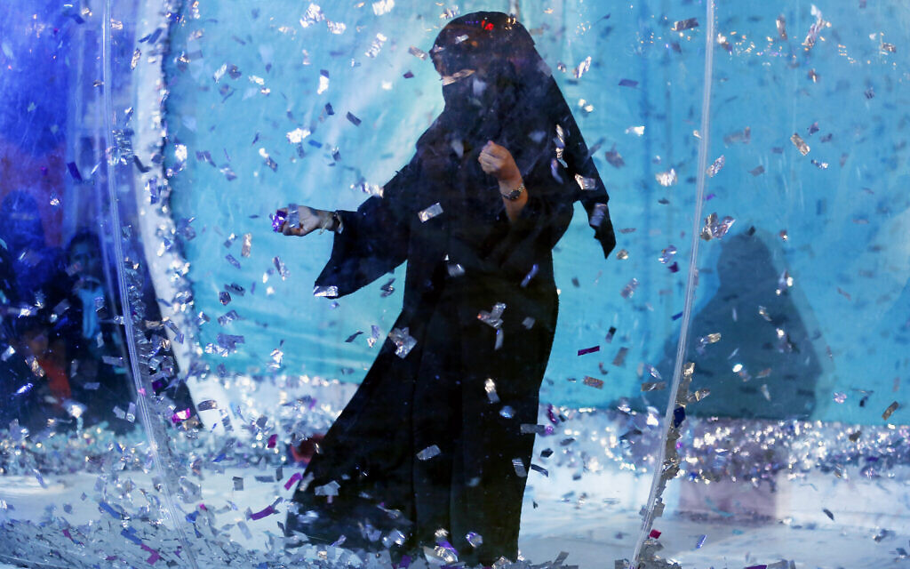 In this December 13, 2019 photo, a woman collects silver tickets as she plays at an amusement park during the Diriyah festival in Diriyah on the outskirts of Riyadh, Saudi Arabia. (AP Photo/Amr Nabil)