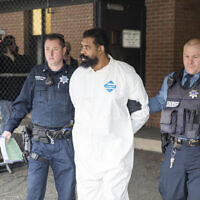 Ramapo police officers escort Grafton Thomas, the suspect in a stabbing spree at a rabbi's home in Monsey, from Ramapo Town Hall to a police vehicle, December 29, 2019, in Ramapo, New York. (AP Photo/Julius Constantine Motal)