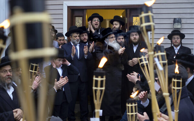 Community members celebrate the arrival of a new Torah at Chaim Rottenberg's residence, Sunday, Dec. 29, 2019, in Monsey, N.Y. A day earlier, a knife-wielding man stormed into the home and stabbed multiple people as they celebrated Hanukkah in the Orthodox Jewish community. (AP Photo/Craig Ruttle)