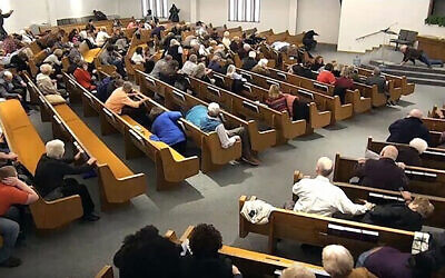 In this still frame from livestreamed video provided by law enforcement, churchgoers take cover while a congregant armed with a handgun, top left, engages a man who opened fire, near top center just right of windows, during a service at West Freeway Church of Christ, Sunday, Dec. 29, 2019, in White Settlement, Texas. (West Freeway Church of Christ/Courtesy of Law Enforcement via AP)