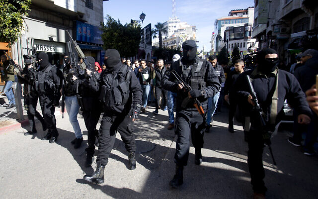 Masked Palestinians carry weapons during a celebration marking the 55th anniversary of the Fatah movement, in the West Bank city of Ramallah, December 31, 2019. (AP Photo/Majdi Mohammed)