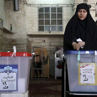 An Iranian voter casts her ballot during the 2017 presidential and municipal council election at a polling station in the city of Qom, 78 miles (125 kilometers) south of the capital Tehran, Iran, May 19, 2017. (AP Photo/Ebrahim Noroozi)