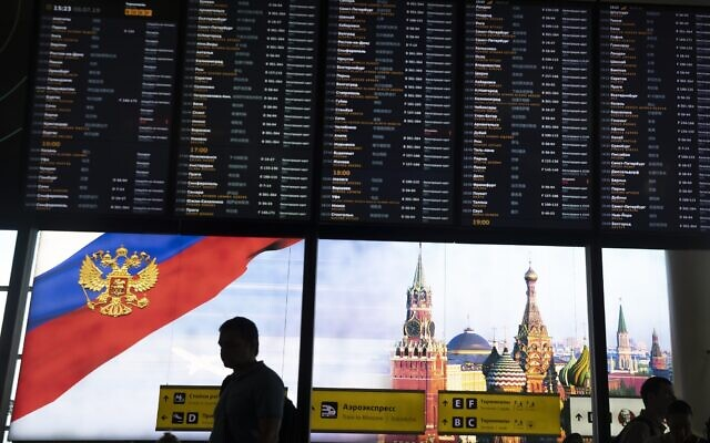 Illustrative: Passengers walk past a departure board at Sheremetyevo international airport in Moscow, Russia, July 8, 2019. (Pavel Golovkin/AP)