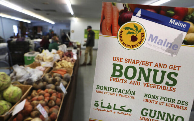 In this photo from March 17, 2017, a sign advertises a program that allows food stamp recipients to use their EBT cards to shop at a farmer's market in Topsham, Maine. (AP Photo/Robert F. Bukaty, File)