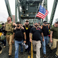 "Illustrative: Members of the Proud Boys and other right-wing demonstrators march across the Hawthorne Bridge during an ""End Domestic Terrorism"" rally in Portland, Ore., on Saturday, Aug. 17, 2019. (AP Photo/Noah Berger)"