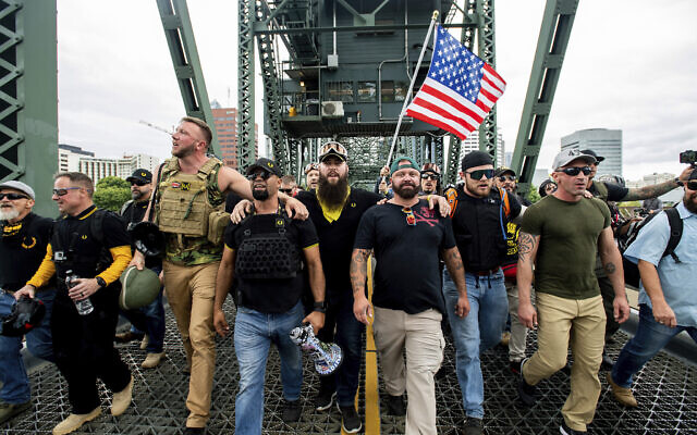 """Illustrative: Members of the Proud Boys and other right-wing demonstrators march across the Hawthorne Bridge during an """"End Domestic Terrorism"""" rally in Portland, Ore., on Saturday, Aug. 17, 2019. (AP Photo/Noah Berger)"""