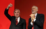 Britain's main opposition Labour Party Shadow Chancellor John McDonnell holds up his hand as party leader Jeremy Corbyn applauds after he delivered a speech during the Labour Party Conference at the Brighton Centre in Brighton, England, Monday, Sept. 23, 2019. (AP Photo/Kirsty Wigglesworth)