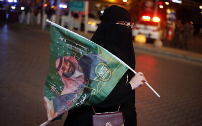 A Saudi woman holds a national flag with picture of Crown Prince Mohammed bin Salman, marking National Day to commemorate the unification of the country as the Kingdom of Saudi Arabia, in Riyadh, Saudi Arabia, September 23, 2019. (AP Photo/Amr Nabil)