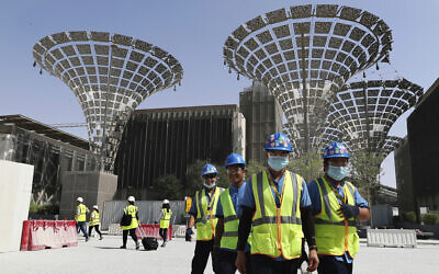 In this photo from October 8, 2019, technicians walk at the three thematic districts at the under construction site of the Expo 2020 in Dubai, United Arab Emirates. (AP Photo/Kamran Jebreili)