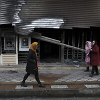 Illustrative: People walk past a bank that was burned during recent protests, in Shahriar, Iran, some 40 kilometers (25 miles) southwest of the capital, Tehran, November 20, 2019. (AP Photo/Vahid Salemi)