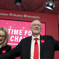 Jeremy Corbyn, Leader of Britain's opposition Labour Party, holds a copy of the manifesto next to Rebecca Long-Bailey on stage at the launch of Labour's General Election manifesto, at Birmingham City University, England, Thursday, Nov. 21, 2019.  (AP Photo/Kirsty Wigglesworth)