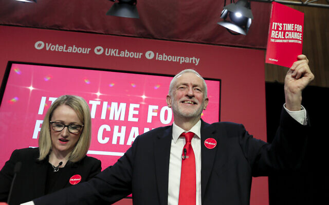 Jeremy Corbyn, former Leader of Britain's opposition Labour Party, holds a copy of the manifesto next to Rebecca Long-Bailey on stage at the launch of Labour's General Election manifesto, at Birmingham City University, England, Thursday, Nov. 21, 2019.  (AP Photo/Kirsty Wigglesworth)