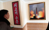 In this Nov. 26, 2019, photo, a man looks at a photo of the launch of a missile hanging on the wall of a factory workers' dormitory in Pyongyang, North Korea. (AP/Dita Alangkara)