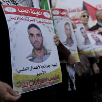 Protesters fly Palestinian flags and carry posters with pictures of Sami Abu Diak,  in the West Bank city of Ramallah, Nov. 26. 2019 (AP Photo/Nasser Nasser)