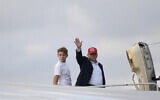 US President Donald Trump, standing with his son Barron, waves from the top of the steps of Air Force One at Palm Beach International Airport in West Palm Beach, Fla., Sunday, Dec. 1, 2019.  (AP Photo/Susan Walsh)
