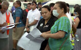 In this image from video, people gather outside a health emergency operation center Dec. 5, 2019, in Apia, Samoa (TVNZ via AP)