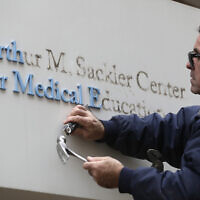 Worker Gabe Ryan removes a sign that includes the name Arthur M. Sackler at an entrance to Tufts School of Medicine, December 5, 2019, in Boston. (AP Photo/Steven Senne)