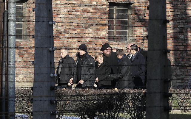 German Chancellor Angela Merkel, center, and Polish Prime Minister Mateusz Morawiecki, right, visit the former Nazi concentration camp of Auschwitz-Birkenau in Oswiecim, Poland on Friday, Dec. 6, 2019 (Markus Schreiber)